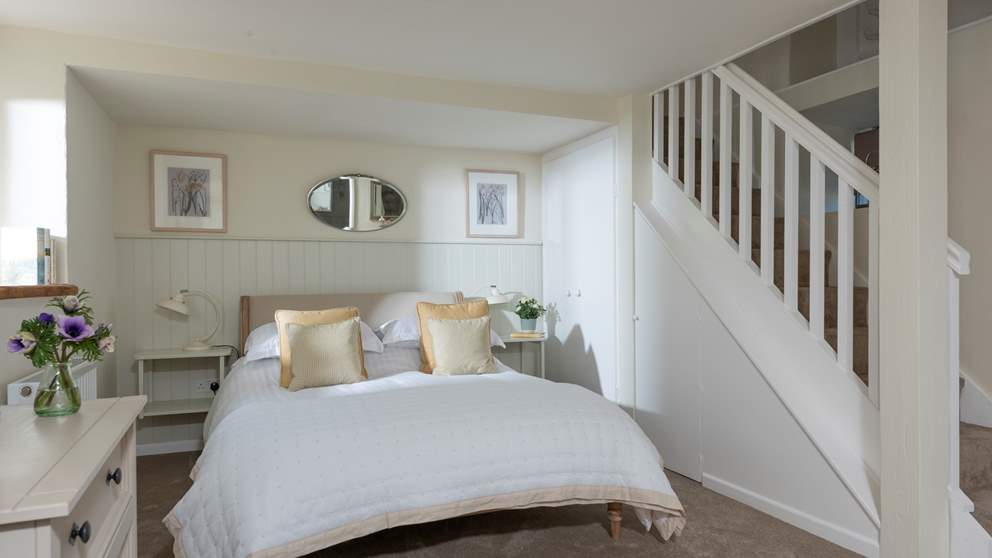 The quiet and spacious bedroom is on the ground floor, king-sized bed bedecked with luscious linens, throws and cushions.