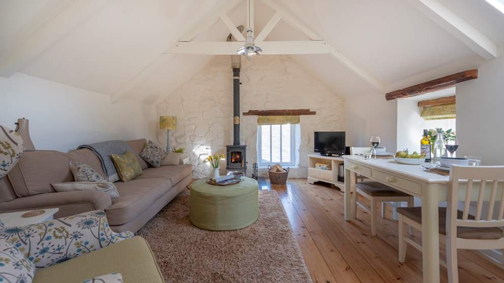 The layout is reversed so the living area is upstairs with gorgeous warm wooden floors, a big sofa ideally placed near the wood burner.