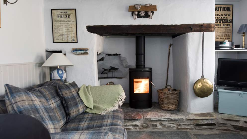 The gorgeous living area, complete with comfy tartan sofa and chair, stunning original flagstone slate flooring and huge inglenook fireplace and wood burner.