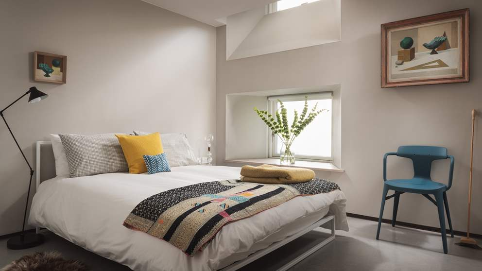 The second bedroom is also king size but offers a more cosy space with dove grey walls and a low-lying window.