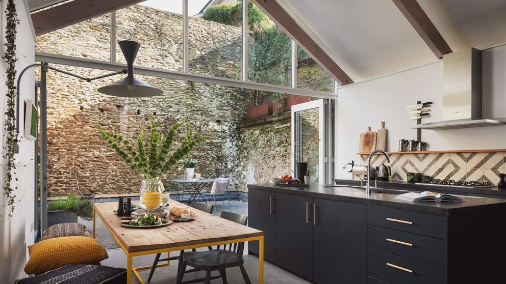 The kitchen and dining area is an incredible space with sleek concrete flooring, black cabinets and worktops.