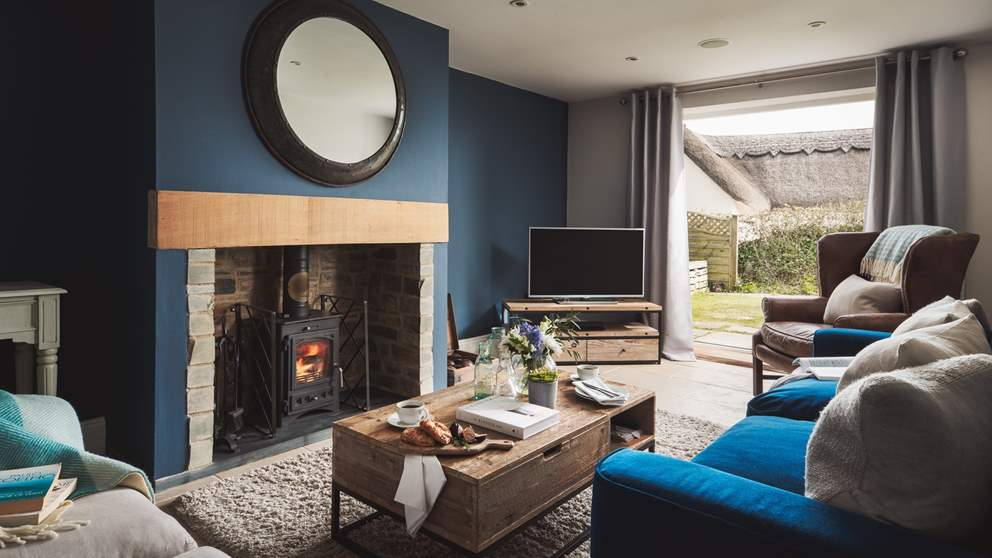 The cosy sitting room in decadent blues is a wonderful retreat at the end of an autumnal day, where its flickering wood burner awaits