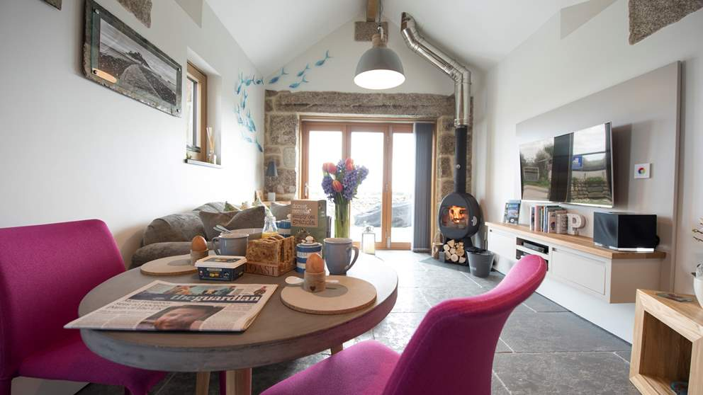 Cosy yet bright, the living space is dominated by the floor-to-ceiling glass door at one end that overlooks the Cornish countryside and the coastline beyond.