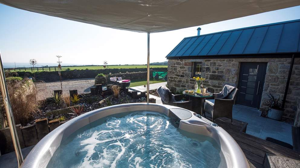 The fabulous hot tub tucked away on the decking but with glorious sea views.