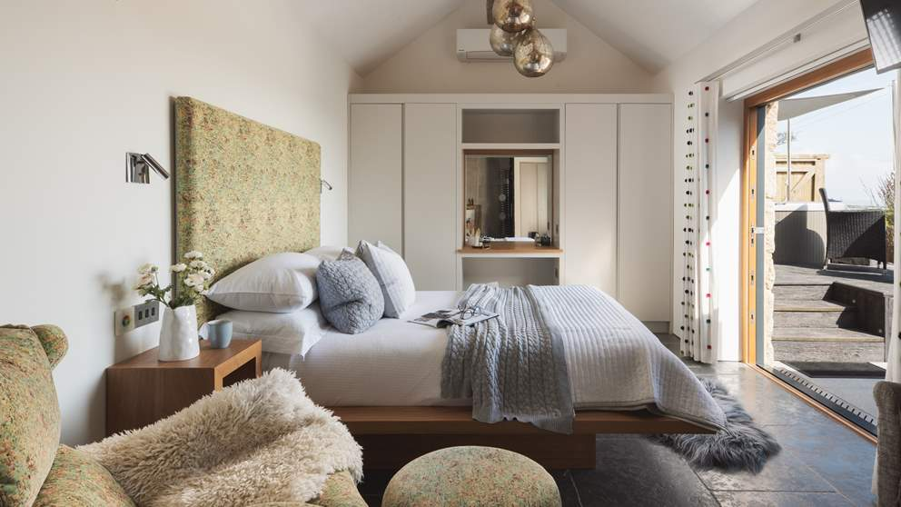 The beautiful bedroom, with underfloor heating and bi-fold glass doors, just steps from the hot tub