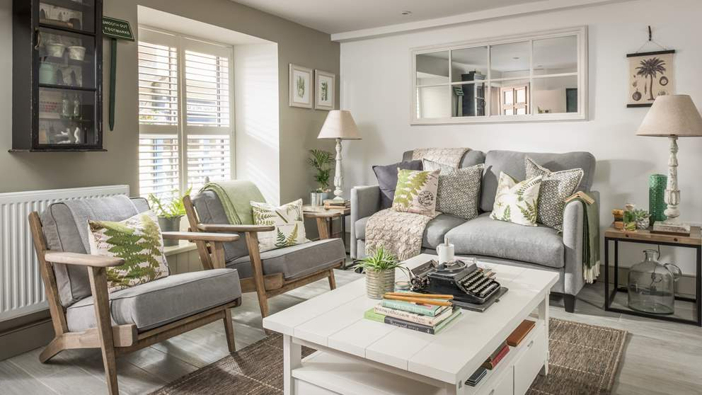 The pretty main space is true to its botanical theme with a soft grey sofa and matching chairs, highlighted in shades of green to compliment the plants that live there.
