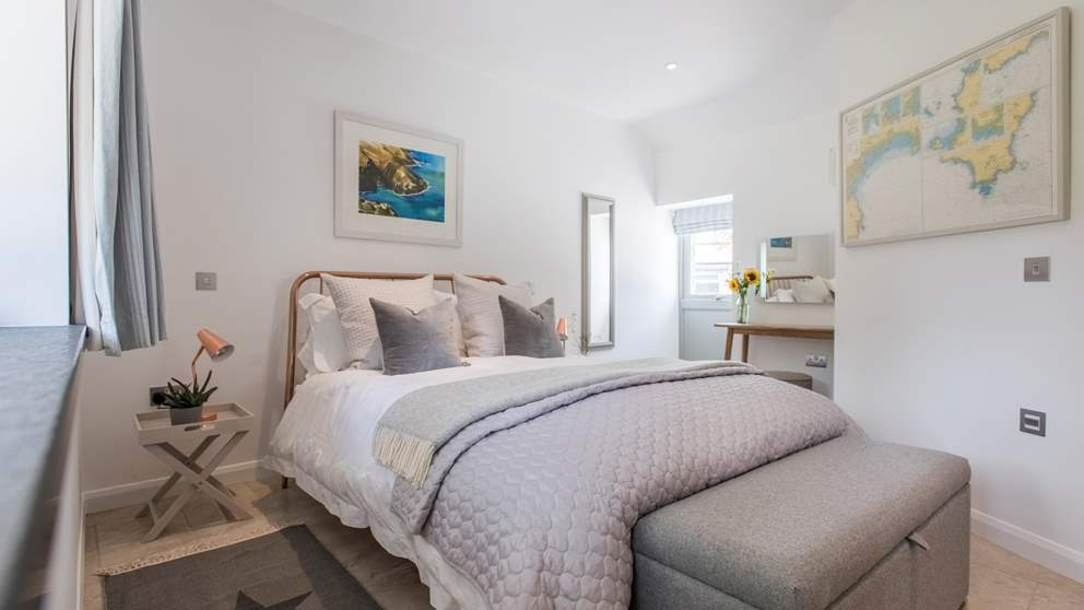 The gorgeous en suite bedroom has a king size bed, covered in swathes of White Company linens and throws.