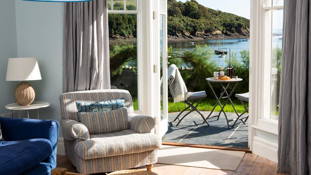 The fantastic sitting room - complete with huge sofas, stripped floorboards and stunning glass doors that open out to the garden overlooking the sea.