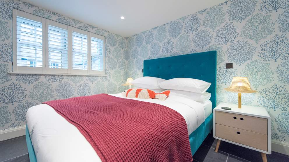 We love the warm coral-themed wallpaper, quirky lamps and sumptuous velvet bed.