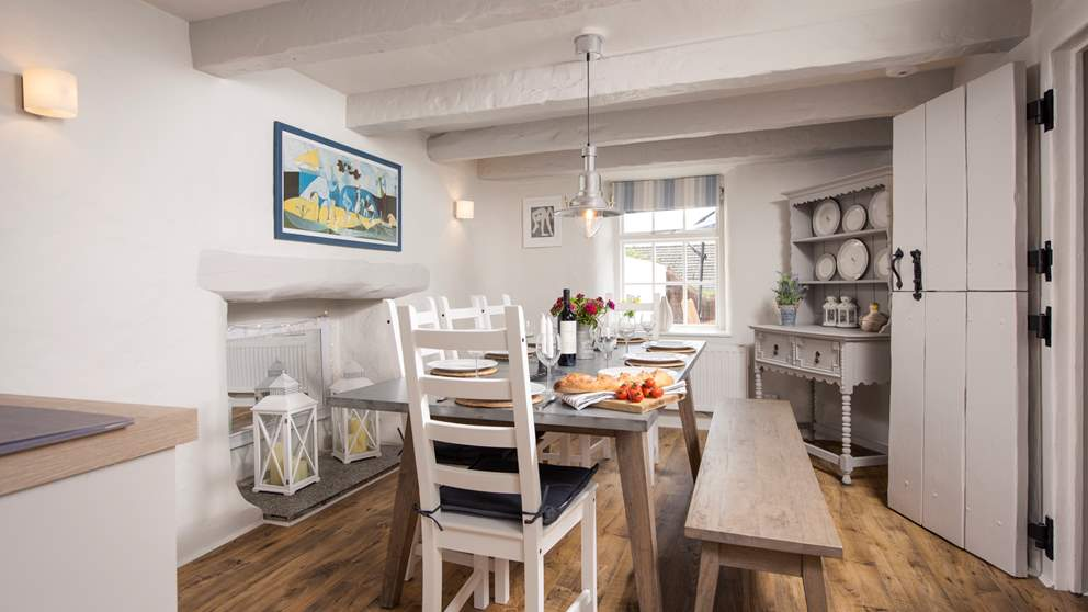 The open-plan kitchen and dining area offers plenty of space for entertaining, with wooden floors, whitewashed walls and beamed ceilings throughout