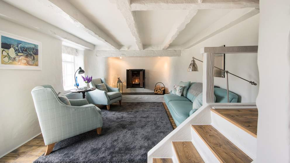 The gorgeously snug living area is simply decorated with rough whitewashed walls, beamed ceiling and a fireplace