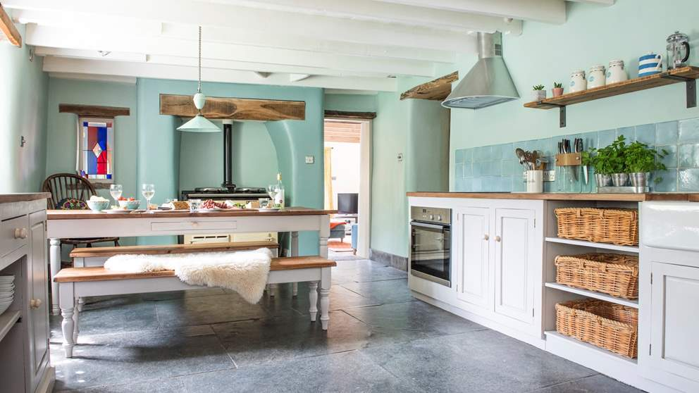 The cottage kitchen with original slate flagstone flooring (now warmed by underfloor heating), exposed beams, wooden worktops and a Belfast sink.
