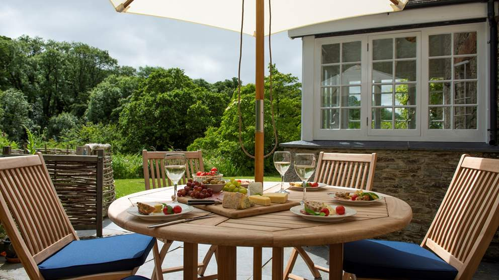 There's a sunny terrace outside the snug complete with dining table, chairs and a parasol.