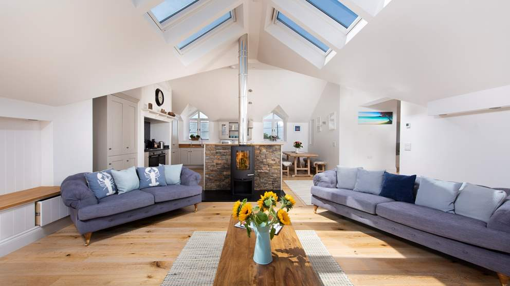 The beautifully light and open-plan living space, with a cosy log-burner nestled in the centre.