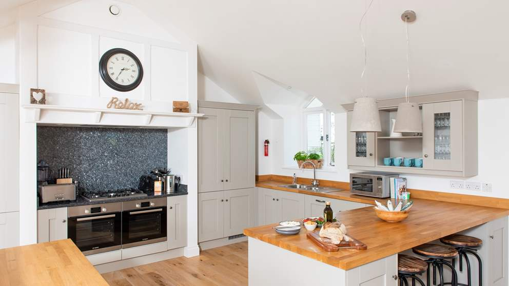 Beautifully appointed and well equipped, this grey and wood kitchen has everything a culinary chef could ask for.