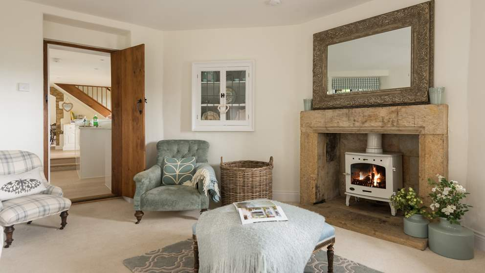 The pretty cream wood burner matches perfectly with the blue tones of this gorgeous sitting room.