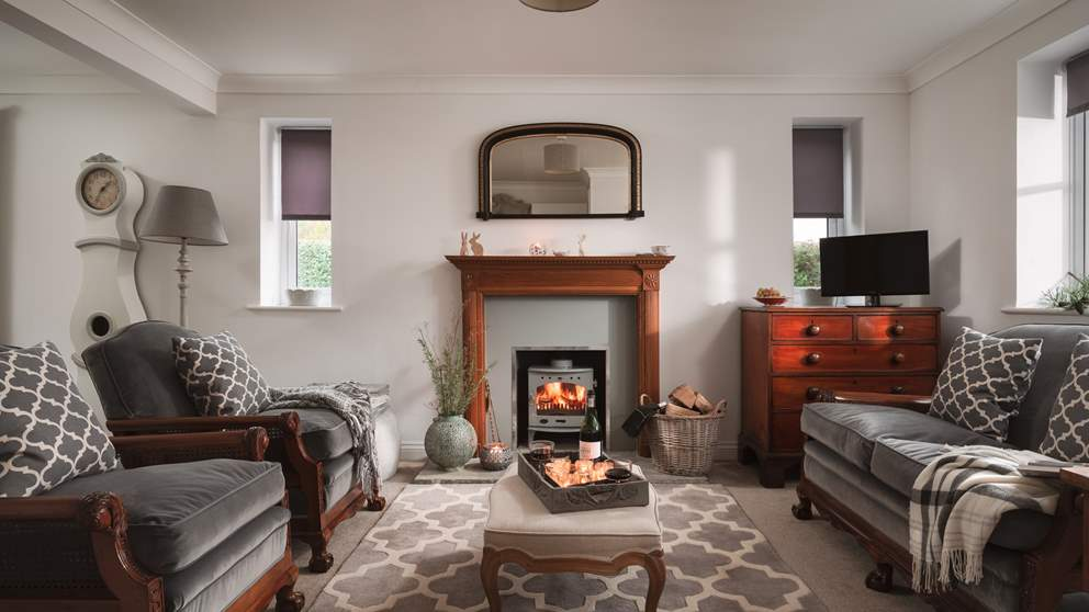 The sitting room is just stunning with a pretty and bijoux wood burning stove and gorgeous antique grey velvet and wood antique chairs and sofa.