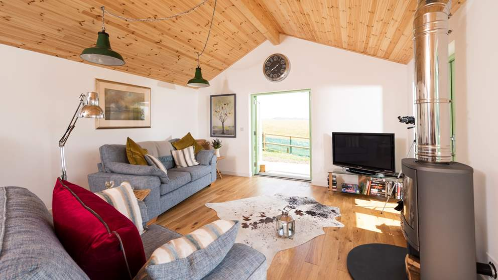 The pretty living space has breathtaking views from each window, plus the huge wood burner makes things extra cosy during winter months.