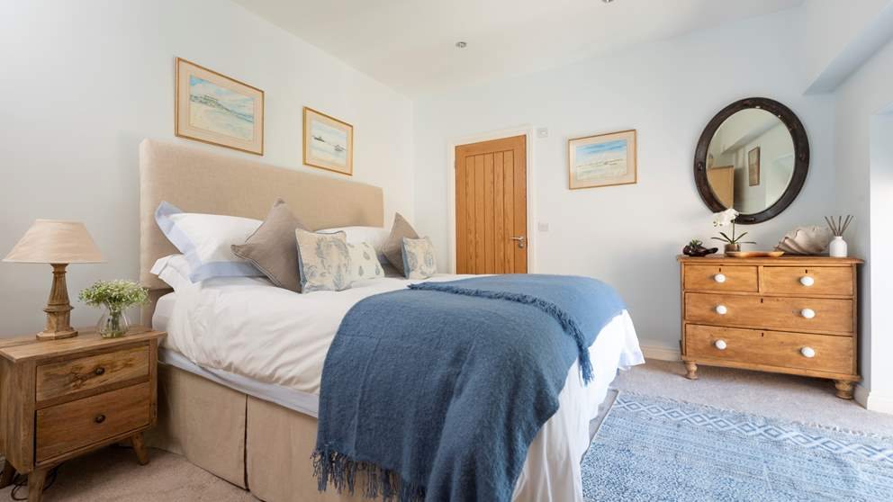 The master bedroom has a luxuriously soft super king and is a pretty melange of blues and light greys, complete with en suite bath and shower.