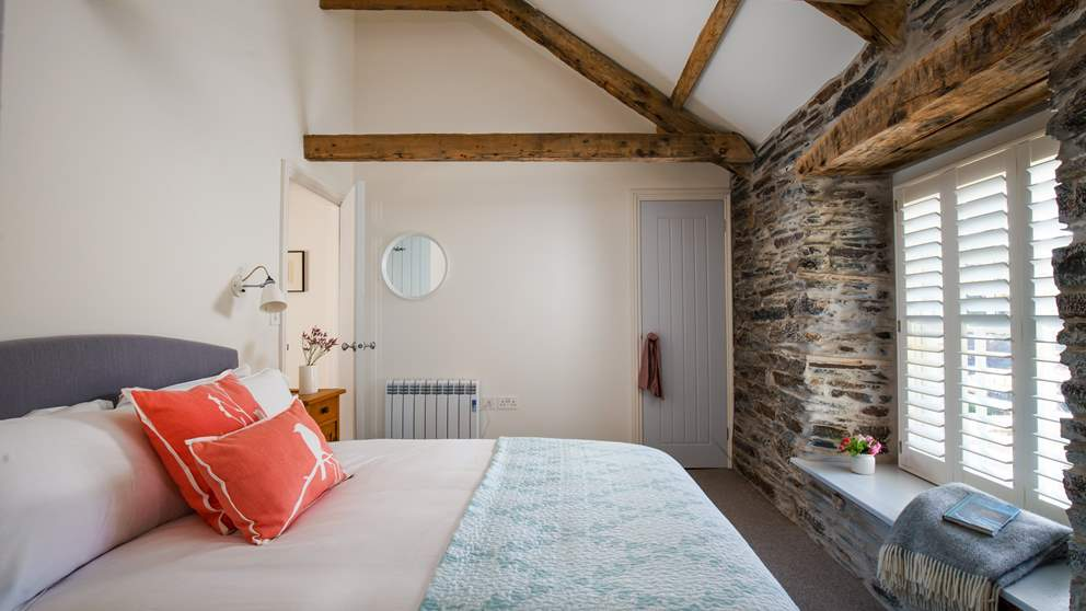 The gorgeous stone walls are a real focal point in this pretty bedroom.
