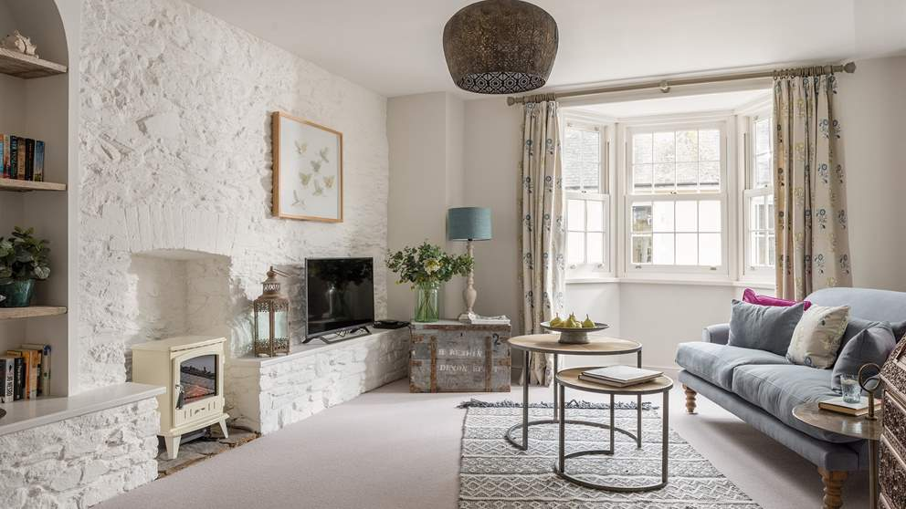 The main living space, with exposed stone walls simply whitewashed, a gas effect cream wood burning stove and super-comfy sofa.