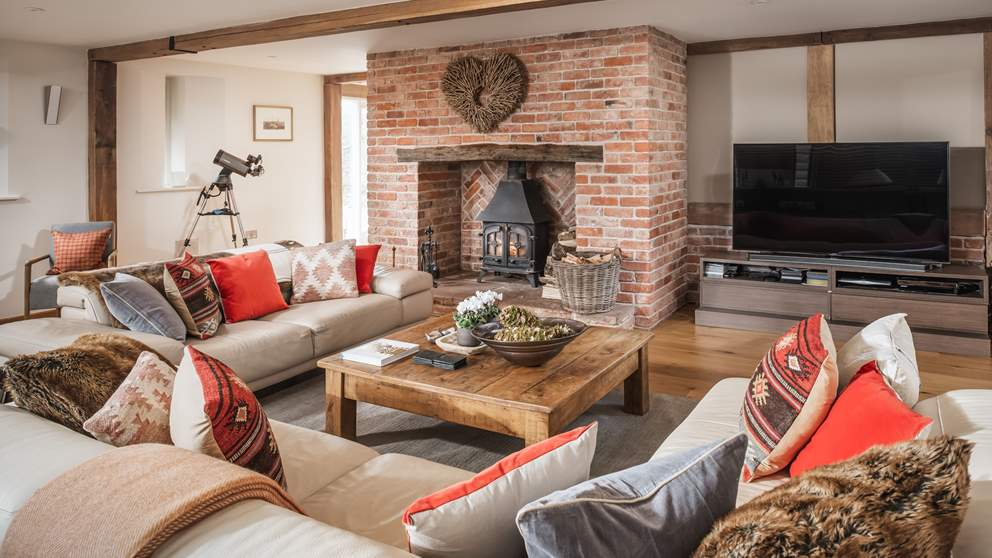 The main living area with a red brick fireplace housing a wood burning stove, plenty of soft, sumptuous sofas to sprawl out on and a 64-inch UHD curved Smart TV.