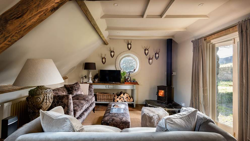 The pretty sitting room and wood burner is the perfect spot for lazy afternoons or evenings curled up on the sofas.