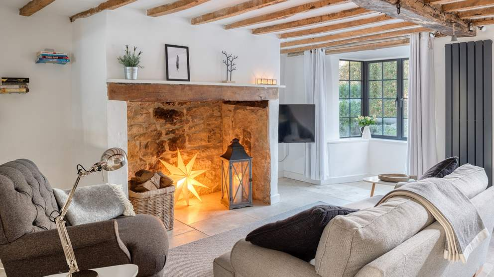 The cosy sitting room is just delightful - the original exposed beams and eye-catching bay window.