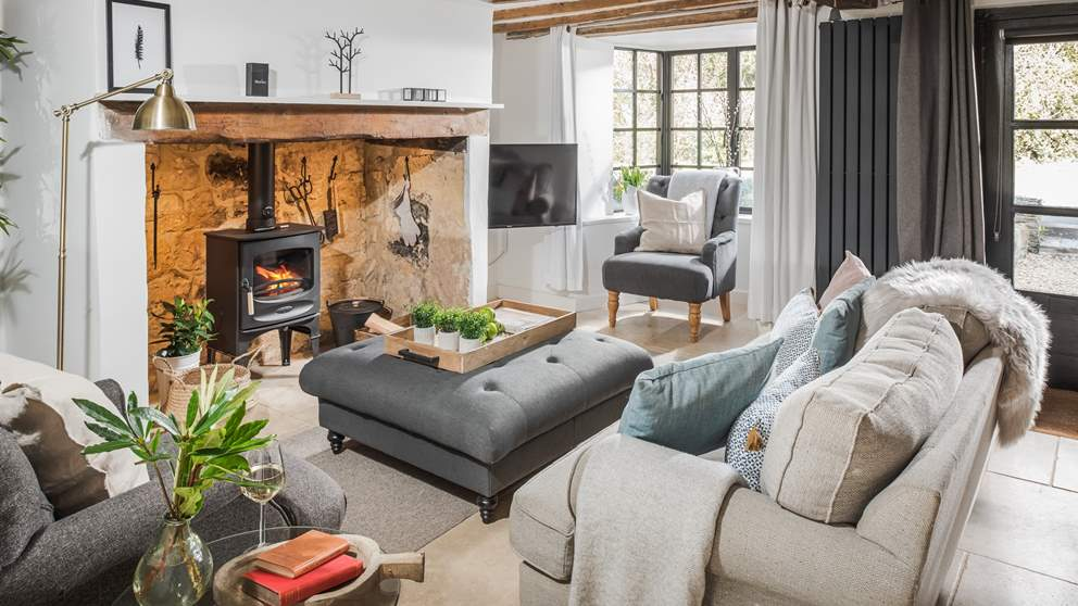 The pretty sitting room with flickering wood burner is a welcome sight