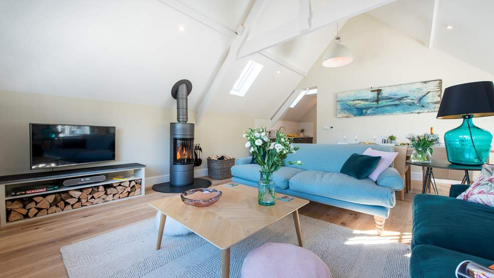 There are two comfy sofas perfectly positioned to gaze out of the windows whilst also nestled around the lovely wood burning stove