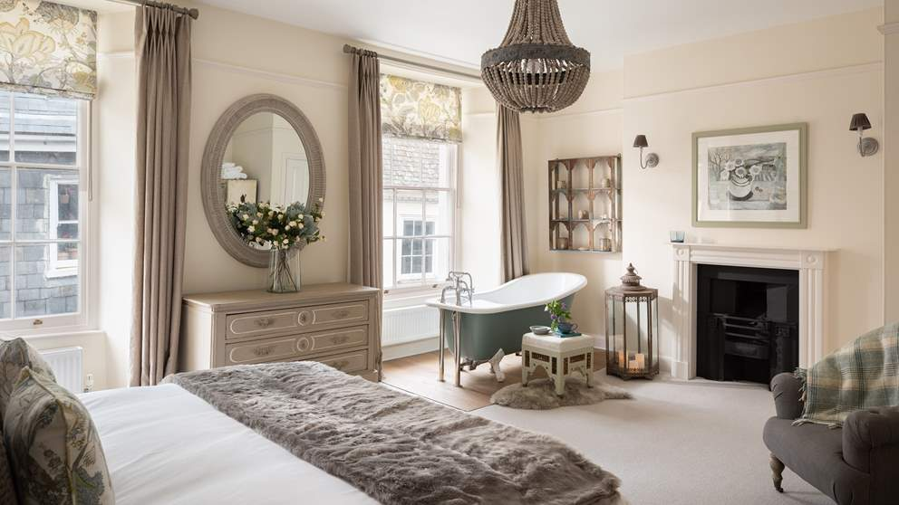 The master bedroom on the second floor, with two gorgeous sash windows, huge super king bed, original fireplace and the pièce de résistance, a wonderful bath.