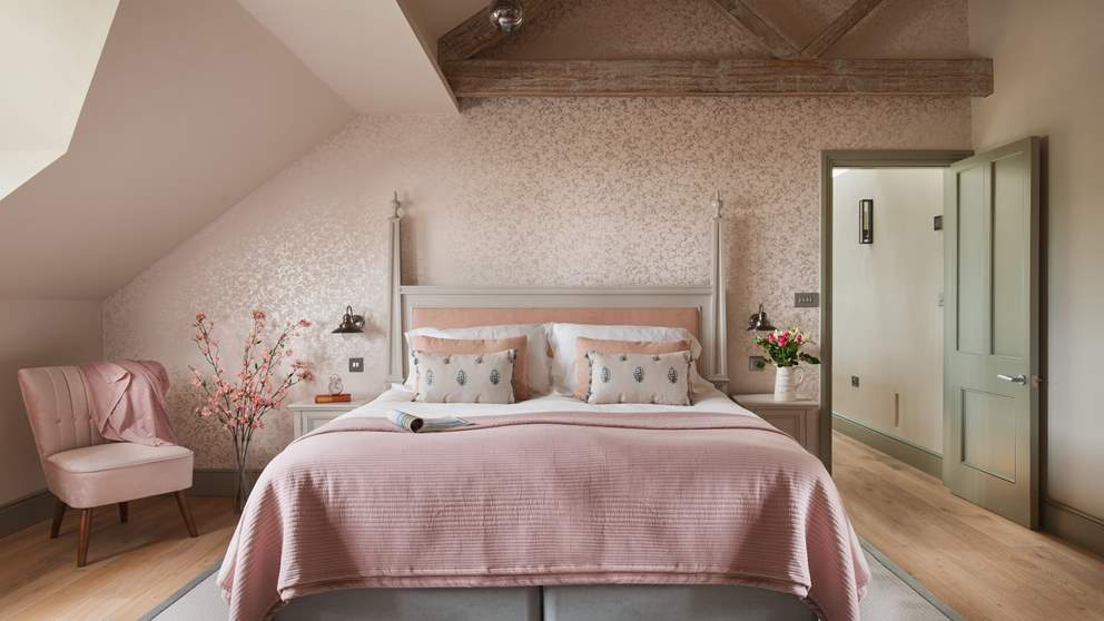 Bedroom 2 in pretty shades of dusky pink and silver, complete with a super-king bed and triple-aspect windows.