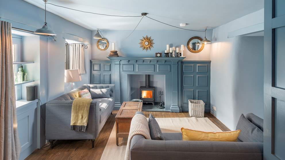 The cosy snug area with two dove grey sofas and a gorgeous ornamental fireplace with roaring Chesney wood burner.