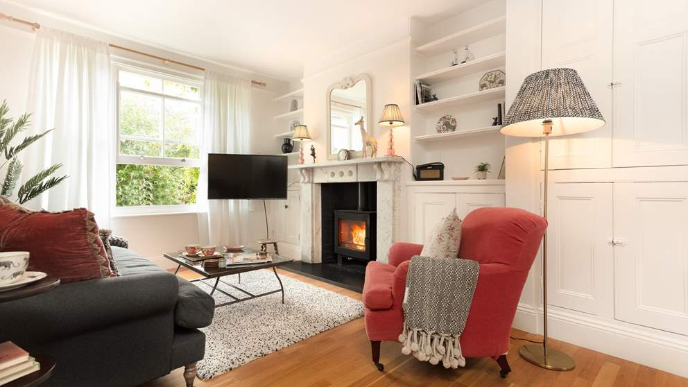 The sitting room lies to the front of the house and is a pretty, cosy spot with a striking marble fireplace and a fabulous wood burning stove.