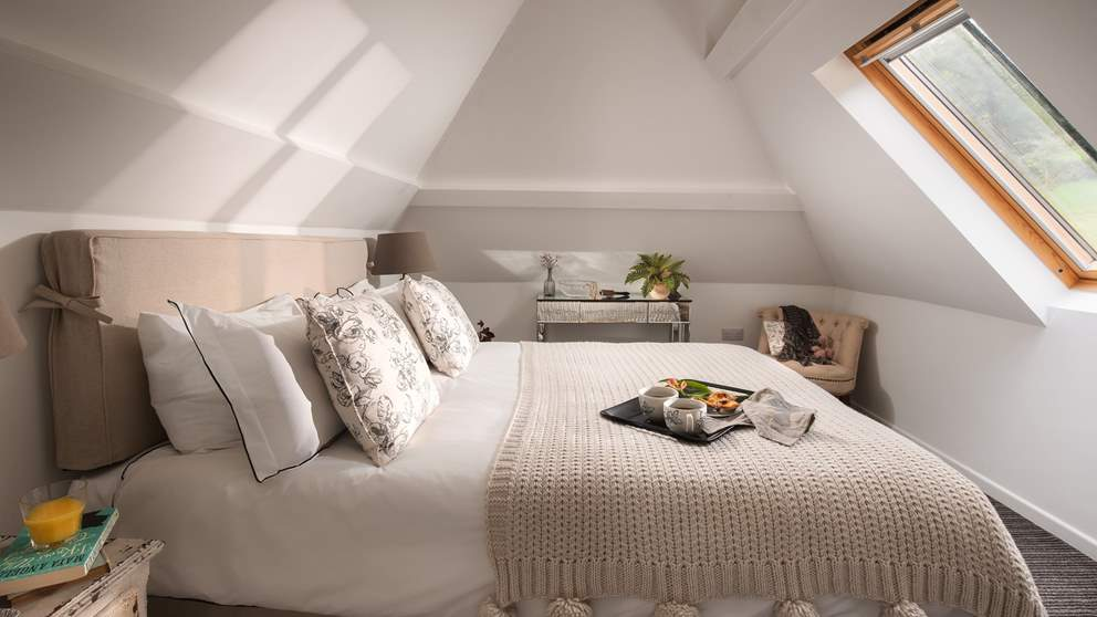 Up in the eaves you'll find a super-romantic county style king size bed.