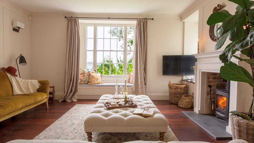The pretty sitting room with roaring wood burner is a perfectly peaceful spot - and we love the window seat