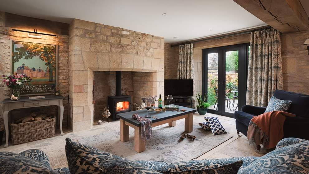 The large, striking sitting room is beautiful with exposed stone walls, original  flag floors, wooden beam and large fire with wood burning stove