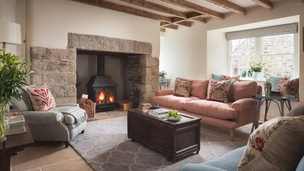 Wooden beams and an exposed stone fireplace add the country-cottage ambience.