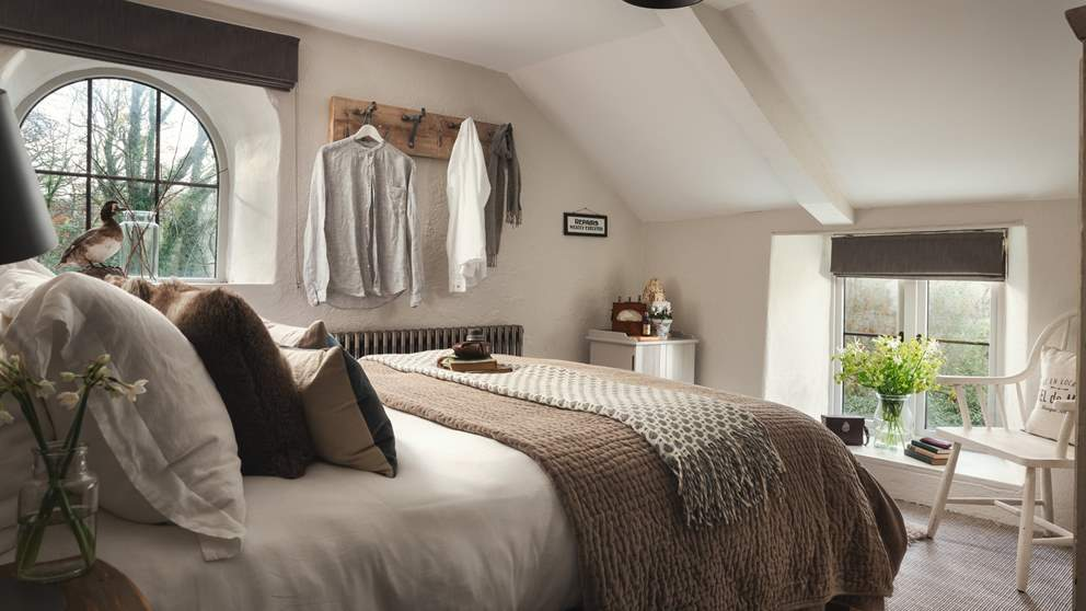 Utterly romantic and oh-so-beautiful with its natural, vintage style, the bedroom with king sized bed boasts dual-aspect windows