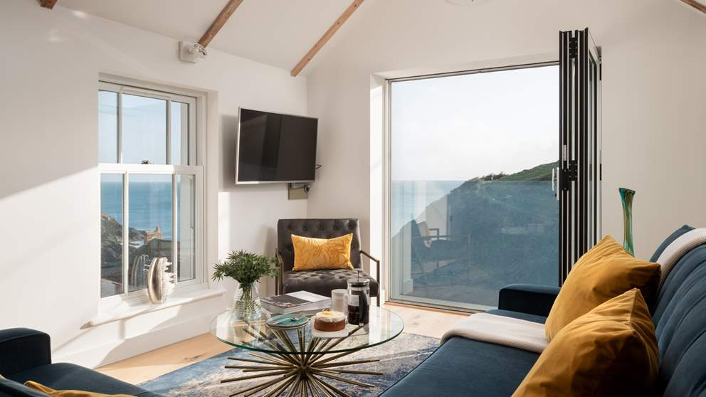 Bi-fold windows at the far end of the room can be pulled back on warmer days to let the blissful sea breezes in