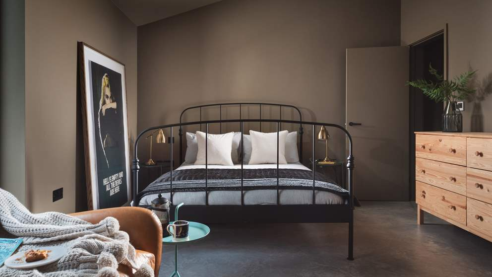 The master bedroom with en suite is chicly romantic with dark walls and a king size wrought iron bed
