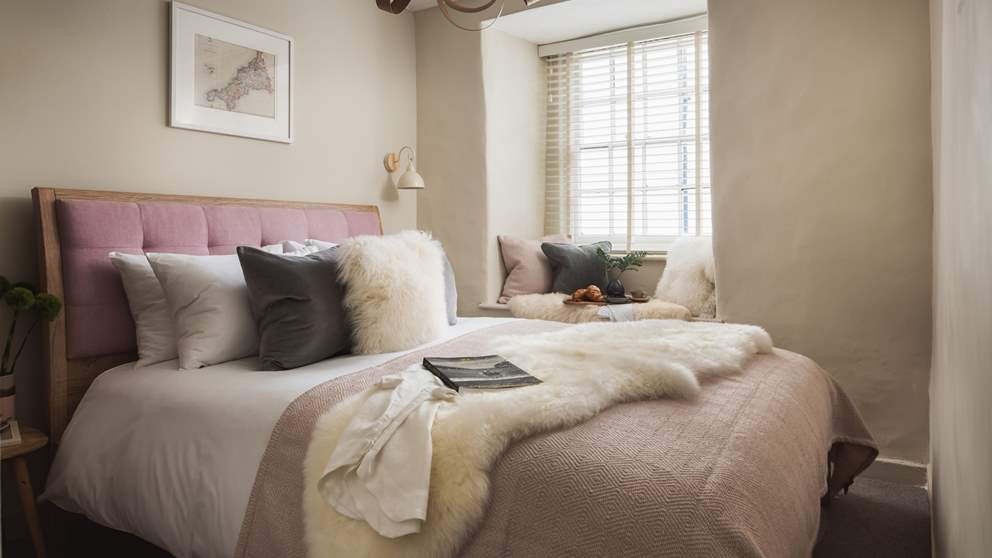 The master bedroom is super-pretty with a sumptuous king size bed with dusky pink headboard