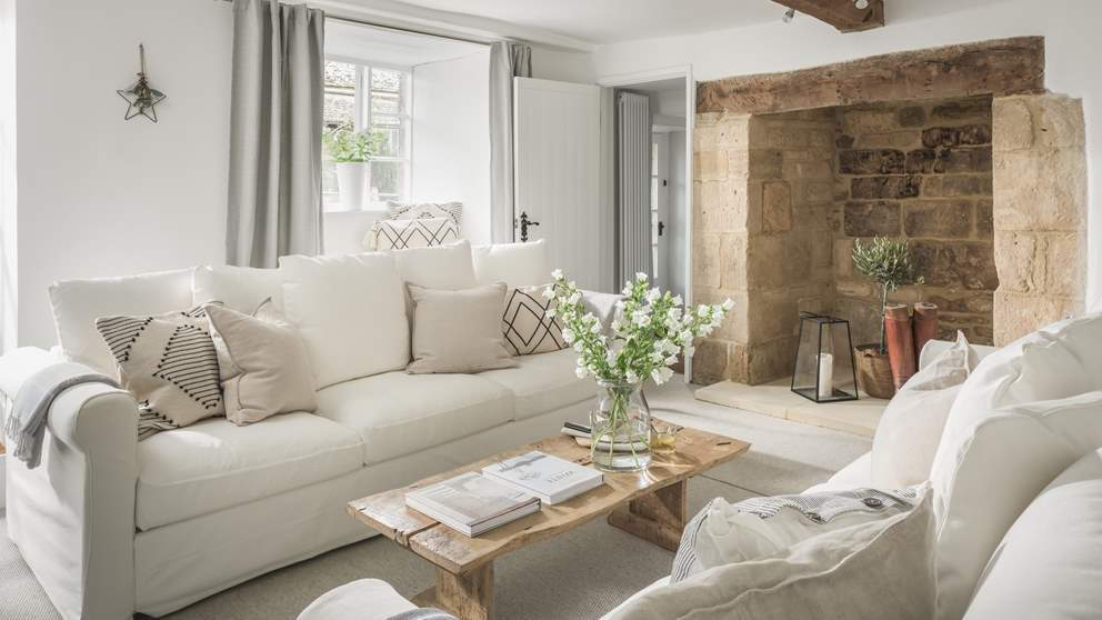 The exquisite sitting room is resplendent in pale, calming shades with original beams and the large inglenook fireplace