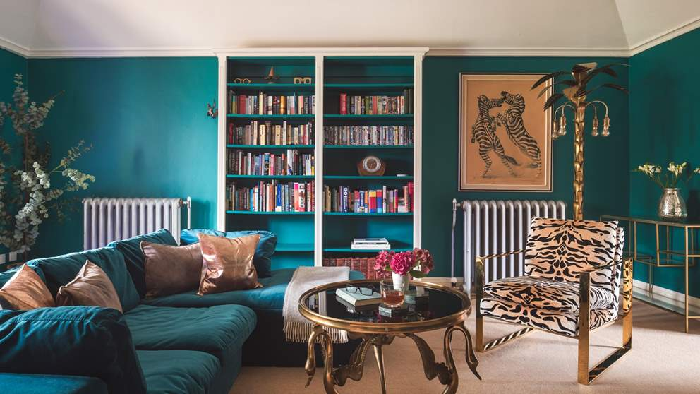 On the first floor, the second sitting room is chic in shades of teal, offering a super sumptuous velvet sofa for sprawling