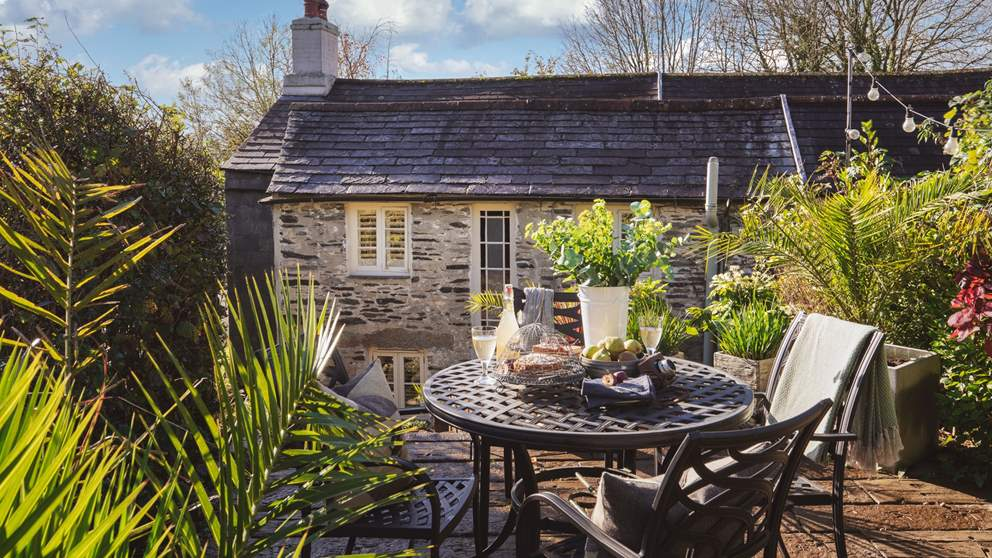 To the back of the property is a raised courtyard with dining table and chairs, perfect for alfresco meals, whilst a charcoal barbeque means you can cook outside too