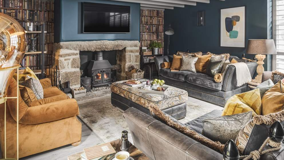 The elegant sitting room in shades of teal, grey and gold is home to sumptuous sofas nestling around the flickering wood burner
