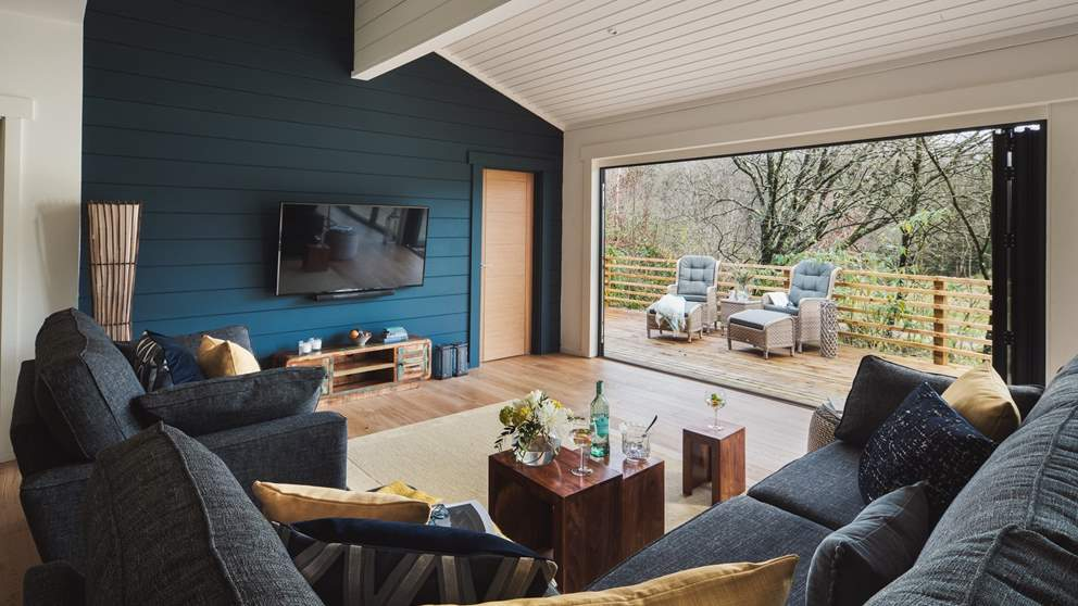 The open plan livingg area is a bright, airy space with floor-to-ceiling bi-folding glass doors that lead out on to the decking