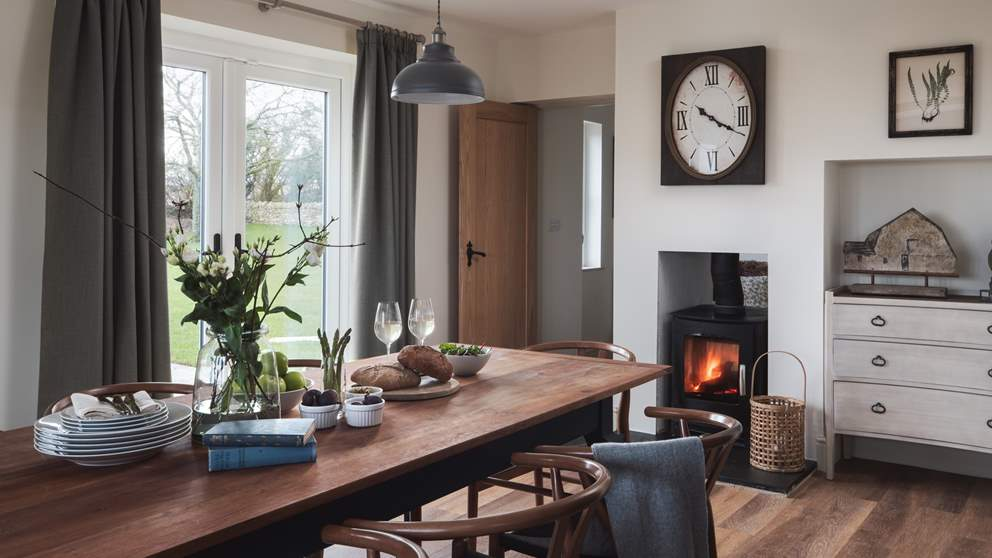 The beautiful dining table comfortably seats ten and benefits from the cosy heat of the double-sided wood burner