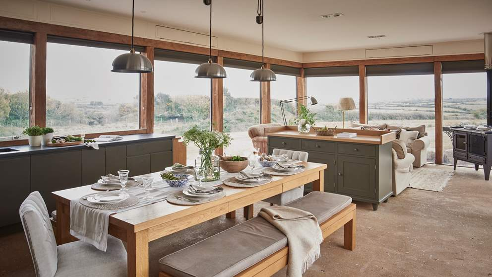The amazing kitchen and dining room is surrounded by floor-to-ceiling glass windows