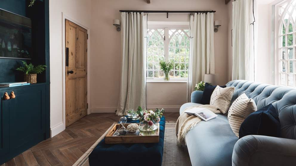 We just love the blue velvet sofa and the incredible vintage windows
